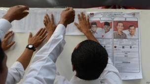 Poll workers post voters list at a polling centre in Jakarta next to a poster showing the two presidential candidates Prabowo Subianto (L) with running mate Hatta Rajasa and Joko Widodo with running mate Jusuf Kalla (R) as voting opens in Jakarta on 9 July, 2014