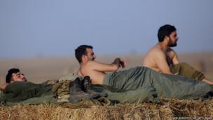 Israeli soldiers wake up on Israel's border with the Gaza Strip on 8 July 2014