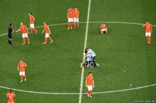 Argentina's midfielder Javier Mascherana and defender Ezequiel Garay (centre) celebrate at the Dutch players leave the pitch