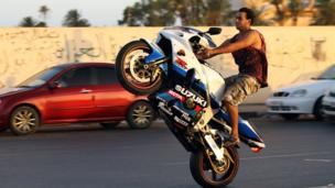 A man on a motorbike doing a wheelie in Benghazi, Libya - Friday 4 July 2014