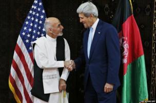 US Secretary of State John Kerry shakes hands with Ashraf Ghani