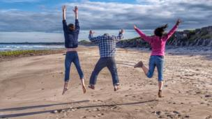 Family jumping on the beach