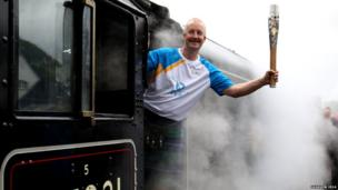 David Sedgwick holds baton from cab of vintage train as steam billows around him