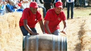 People take part in a wine-barrel rolling competition in Franschoek town, South Africa, on 12 July 2014