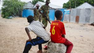 Somali soldiers walk past two boys sitting on a rock, one of them wearing a football jersey, as they patrol in a street of Mogadishu on 15 July 2014