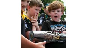 Open-mouthed schoolboy holds baton as his friends admire it