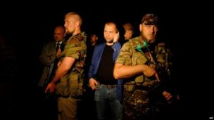 "Self-proclaimed Prime Minister of the pro-Russian separatist ""Donetsk People's Republic"" Alexander Borodai (C) stands as he arrives on the site of the crash"