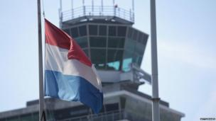 The Dutch flag flies at half mast at Amsterdam's Schiphol Airport in memory of those on Malaysia Flight MH17 (18 July 2014)