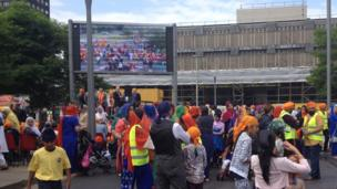 People watching a big screen showing the Sikh festival in Middlesbrough