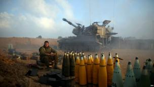An Israeli soldier with tank and artillery shells (21 July 2014)