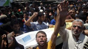 Palestinians carry the body of a member of the Siyam family at a funeral in Rafah, 21 July 2014