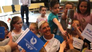 Baton bearer Lee McConnell carries the Glasgow 2014 Queen's Baton at Netherlee Primary School, Clarkston in East Renfrewshire.