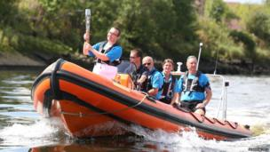 Baton bearer Jordan Robertson carries the Glasgow 2014 Queen's Baton on a boat on the River Clyde in Glasgow.
