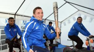Team Scotland boxer Reece McFadden holds the Glasgow 2014 Queen's Baton as he tries to make weight for competition at the Commonwealth Games Athletes' Village in Glasgow.