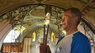 Batonbearer 010 Marty Flett with the Glasgow 2014 Queen's Baton inside the Italian Chapel, Lamb Holm on the Orkney Islands.