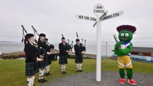 Clyde the the Glasgow 2014 Commonwealth Games mascot and members of the Wick Pipe Band welcome the Glasgow 2014 Queen's Baton to John O'Groats in the Scottish Highlands.