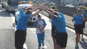 Police Scotland baton escorts create a guard of honour for a relay baton bearer.
