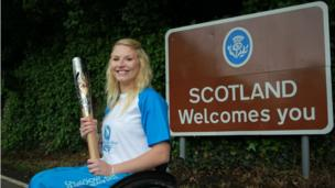 Baton bearer Samantha Kinghorn carries the Glasgow 2014 Queen's Baton through Coldstream in Scottish Borders