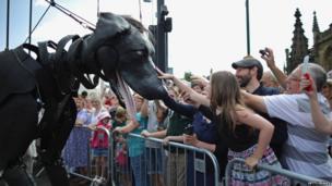Spectators pet a giant puppet dog.