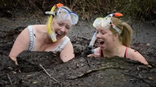 Two women laughing as they get into the bog.