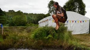 A man is jumping in the air , covered in mud, into the bog Jacuzzi.