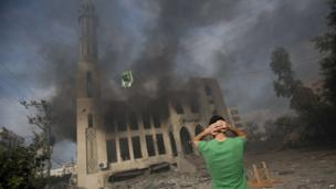A Palestinian man reacts in front of a destroyed mosque after it was hit by an Israeli air strike, on July 29, 2014, in Gaza City.