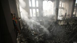 Palestinians extinguish fire at a mosque which witnesses said was hit in an Israeli air strike, in Gaza City