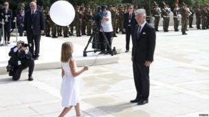 King Philippe of Belgium is handed a balloon by a girl dressed in white in Liege