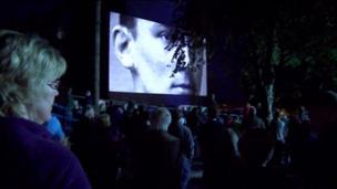 People watch as images of soldiers and civilians are projected onto Bangor's Memorial Arch