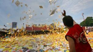 "An ethnic-Chinese Indonesian man throws ""hell money"" prepared as offerings for his ancestors"" souls into the air during the ""hungry ghost"" festival in Medan, North Sumatra, Indonesia, on Sunday, 10 August 2014"