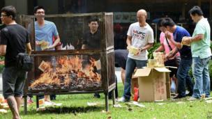 Employees from a nearby office building burn offerings to mark the Hungry Ghost Festival in Singapore on 8 August, 2014