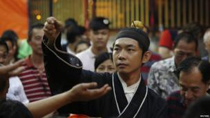 A monk throws coins to worshippers for good luck during preparations for the Hungry Ghost festival in Kuala Lumpur on 3 August, 2014