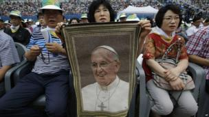 A woman holds a picture of Pope Francis as they wait for Pope's arrival for the Mass of Assumption of Mary at a stadium in Daejeon, south of Seoul, South Korea on Friday, 15 August 2014