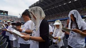 Survivors and relatives of victims of April's Sewol ferry tragedy in which 300 people died listen to a mass attended by Pope Francis at Daejeon World Cup Stadium on Friday, 15 August, 2014