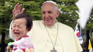 A girl cries after Pope Francis blessed her upon his arrival for the Mass of Assumption of Mary at a stadium in Daejeon, South Korea, on Friday, 15 August, 2014