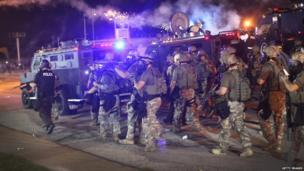 Police advance while sending a volley of tear gas toward demonstrators protesting the killing of teenager Michael Brown in Ferguson, Missouri, 17 August 2014