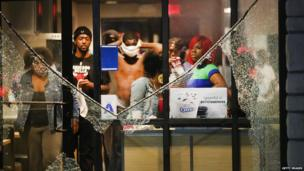People take cover from tear gas inside a McDonald's restaurant after a demonstration in Ferguson, Missouri, 17 August 2014
