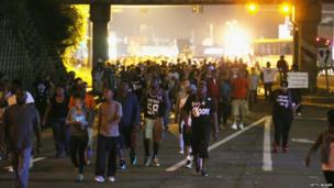 Demonstrators walk down the street as they protest the shooting death of Michael Brown in Ferguson, Missouri, 17 August 2014