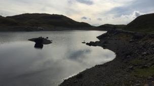 Llyn Llydaw yn llonydd er gwaetha'r tywydd llwm // Llyn Llydaw still resplendent depite the weather