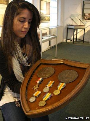 A volunteer shows Arthur and Robert Greg's medals
