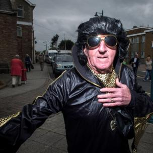 Elvis lookalike in black leather and gold