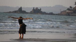 Woman dancing on a beach in Goa, India