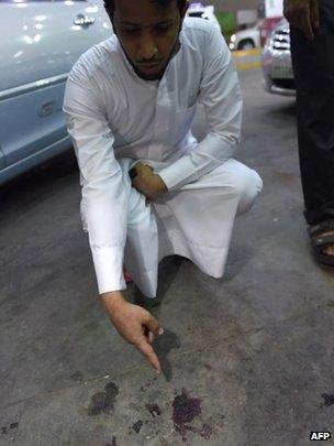 A Saudi official points at a stain of blood on the ground at the scene of Tuesday's shooting in Riyadh. Photo: 14 October 2014