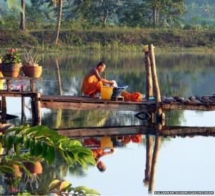 A monk washing his clothes early one morning near a temple in Thailand