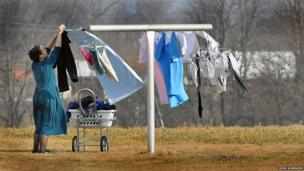 An Amish housewife hanging laundry