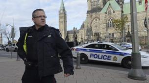 A police officer secures the scene of a shooting on Parliament Hill in Ottawa