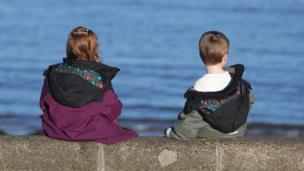 Children sit by the beach