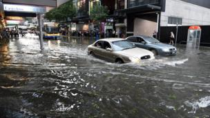 Cars drive through floodwater