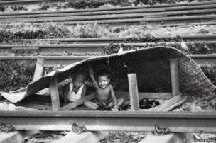 Children make a house under a mat