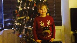 a little boy next to his Christmas tree